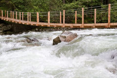 Wooden bridge over wild waters Royalty Free Stock Photo