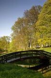 Wooden bridge and park. Small wooden bridge in the park with fresh green trees, grass on the blue sky Stock Image