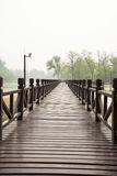 The wooden bridge. The park, brown wooden bridge, and the distant trees Royalty Free Stock Images