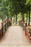 The wooden bridge. In the park, red bridge, green decorative wood, and spring tree Royalty Free Stock Photos