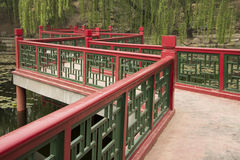 The wooden bridge. In the park, red and green wooden bridge, and willow leaves Stock Photography