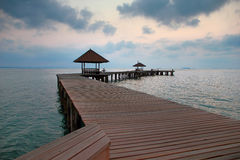 Wooden bridge in the port between sunrise. Royalty Free Stock Images
