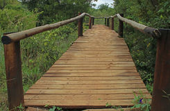 WOODEN BRIDGE WITH POST RAILINGS. Wooden bridge spanning across grassland and river Stock Photos
