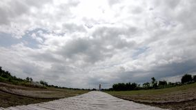 The wooden bridge and The reflection of the Sun with the Rain clouds move fast on the sky in paddy fields.  stock footage