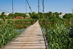 Wooden bridge on a river Stock Photography