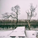 Wooden bridge on the river bank covered in snow Royalty Free Stock Photos