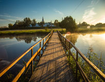 Wooden bridge through river in morning sunlight.  Stock Photography