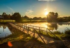 Wooden bridge through river in morning sunlight Stock Photo
