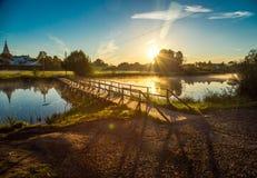 Wooden bridge through river in morning sunlight Stock Photos