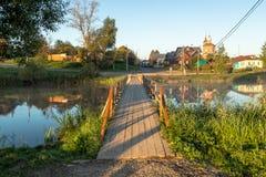 Wooden bridge through river in morning sunlight Stock Photography