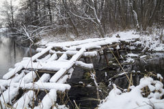 Wooden bridge through river in wood. Wooden bridge through river in winter wood and snow in Russia Royalty Free Stock Photos