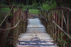 A wooden bridge with rusty metal handrail in a park, a path in to the wood Stock Photo