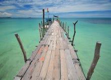 Wooden bridge into the sea Stock Photos
