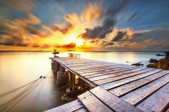 Wooden bridge. Into the sea at sunrise morning with still water by long exposure photography and moving cloudy sky Royalty Free Stock Image