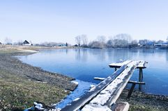 Lake. Wooden bridge on the shore of a frozen lake in the village Royalty Free Stock Photo