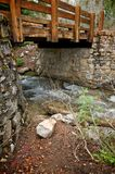 Wooden Bridge Between Stone Walls and Stream Royalty Free Stock Photography