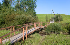 The wooden bridge through a stream to a well Royalty Free Stock Images