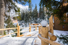 Wooden bridge with streetlights in a snow-covered skiing town. Wooden bridge with streetlights  between old wooden cottages in a snow-covered skiing town on a Stock Images