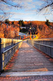 Wooden bridge at sunset. Beautiful nature scene: sun setting over the wooden bridge of a small town on a autumn day Royalty Free Stock Photos