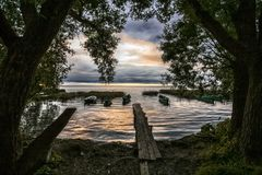 Wooden bridge at sunset. The wooden bridge and boats on the mooring at the autumn coast overlooking a decline in clouds Stock Photography