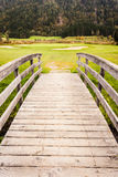 Wooden bridge to golf course. An old wooden bridge on an idyllic meadow or a beautiful golf course Stock Photo