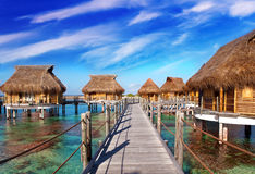 wooden bridge to a hut over water at the ocean royalty free stock photo