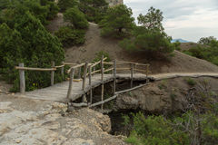 Wooden bridge on Trail Golitsyn - Falcon Path a mountain pathway carved at side of Koba-Kaya. Crimea Stock Photography