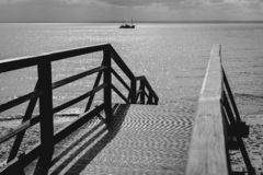 Pier on the background of the sea. Wooden bridge for walks to the beach, black & white stock images