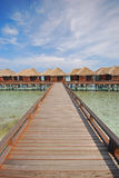 Wooden Bridge Walkway leading to a Row of Overwater Villa Stock Photography