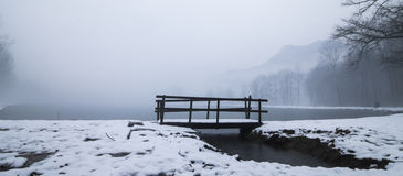 Wooden bridge in a winter lake Royalty Free Stock Photo