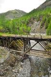 Wooden bridge in Yakutia across the mountain river. Stock Photos