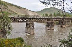 Wooden bridge in Yakutia across the mountain river. Stock Photography