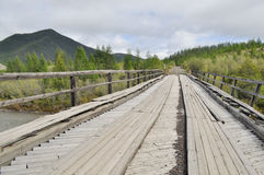 Wooden bridge in Yakutia across the mountain river. Royalty Free Stock Photo
