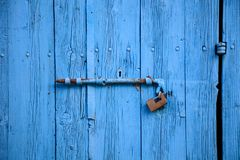 Wooden bright blue, empty, old door for background. Rusty latch, padlock. Close up, banner, details. Wooden bright blue, blank, aged door for backdrop. Rusty Royalty Free Stock Images