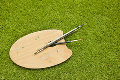 Wooden brown art palette. With brushes on the green grass Stock Image