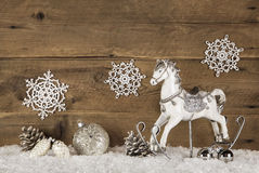 Wooden brown background with a rocking horse on snowy background Stock Image