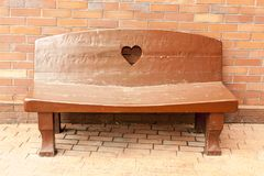 Wooden brown bench with a heart on the back near brick wall on the town street royalty free stock photos