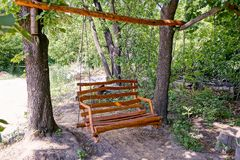Wooden brown bench swing on a wooden beam Stock Photography