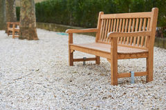 Wooden brown bench on the white ground in park in Paris Royalty Free Stock Image