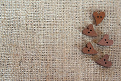 Wooden brown buttons hearts on burlap with space for text Royalty Free Stock Photo