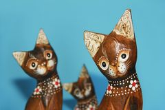 Wooden brown cat souvenirs sit on a blue background. Wooden brown cat souvenirs sit on blue background royalty free stock image