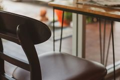 A wooden brown chair placed near wooden table with steel leg wit stock photos