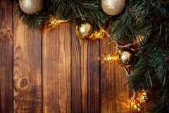 A wooden brown Christmas background with a spruce branch, a New Year`s garland, yellow and gold balls. Empty space. happy new yea