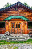 Wooden brown cottage in the countryside with a wheel on porch Stock Photos
