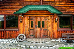 Wooden brown cottage in the countryside with a wheel on porch Stock Image