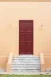 Wooden brown door on orange wall. Ancient wooden brown door on orange wall Royalty Free Stock Photos