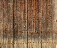 Wooden brown timeworn door. Space for text backdrop, rusty latch and padlock. Closeup view, details. Wooden brown door. Timeworn background with rusty latch and Royalty Free Stock Photography