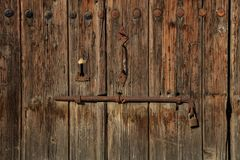 Wooden brown empty timeworn door. Space for text backdrop, rusty latch and padlock. Closeup, details. Wooden brown door. Timeworn blank, banner, background with Royalty Free Stock Photo