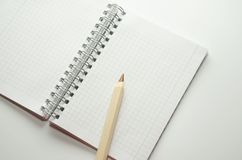 Wooden brown pencil on the background of a blank notepad royalty free stock photo