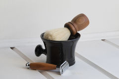 Wooden brown razor, wooden brown brush, black ceramic bowl. Wooden shaving brush in bowl and T-shaped razor Royalty Free Stock Image